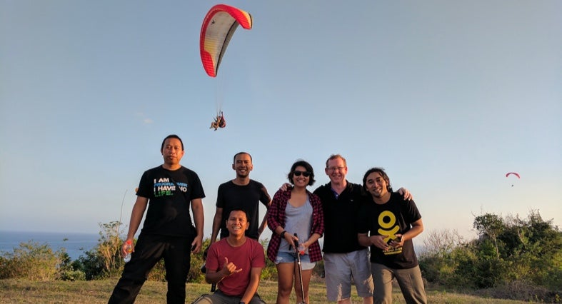 Team members paragliding in Bali