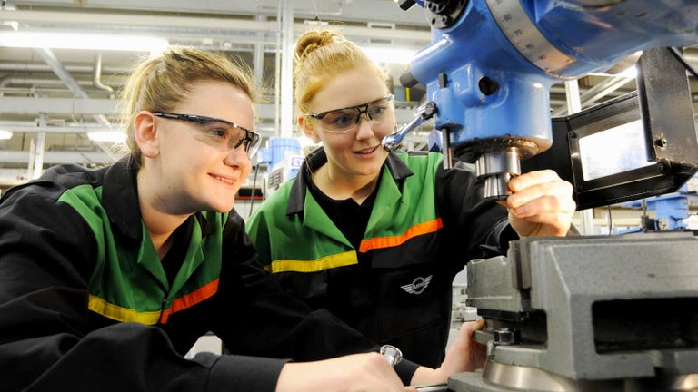 Two students using a piece of machinary