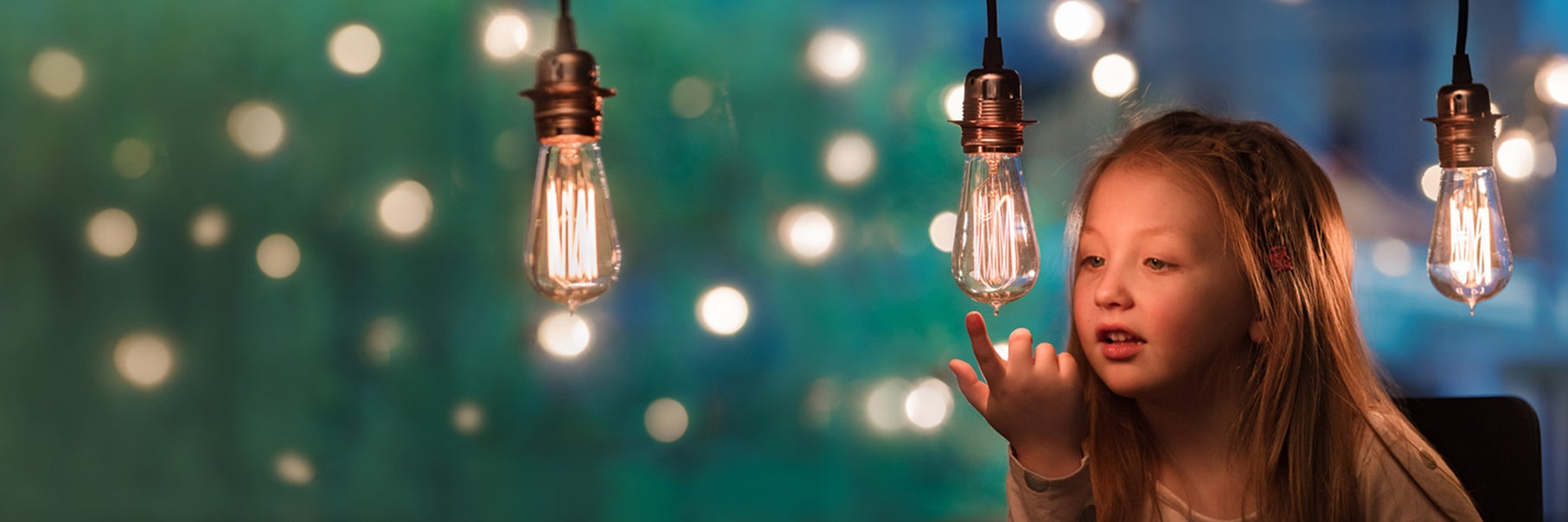 Young child looking at lightbulb