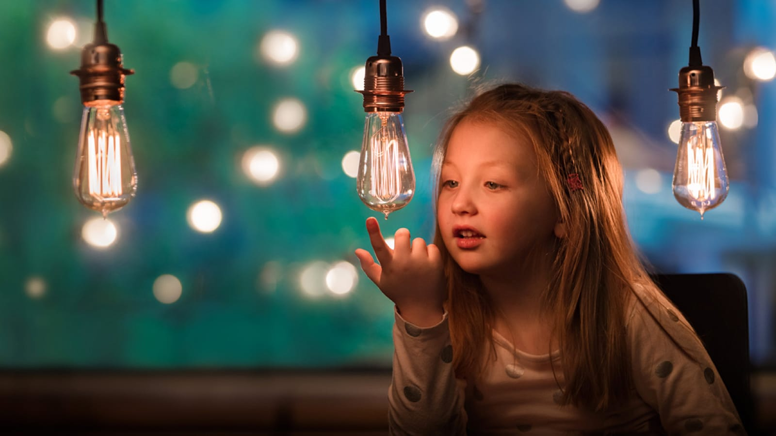 Young girl looking at light bulbs