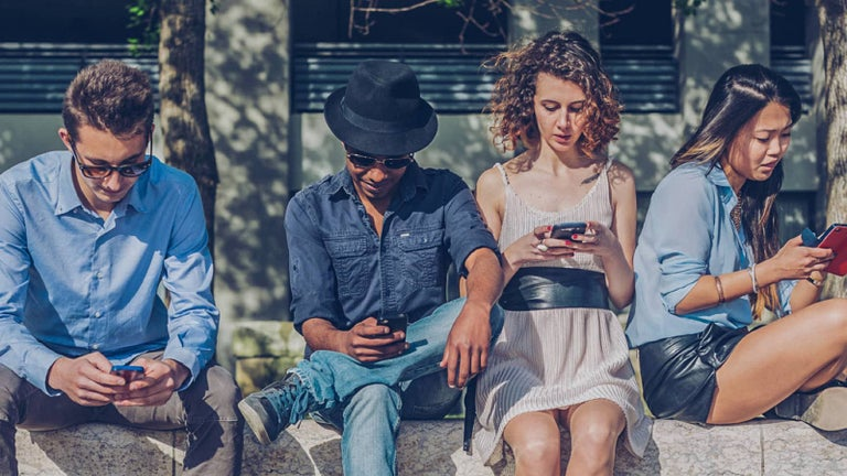 Four young people looking at their mobile phones